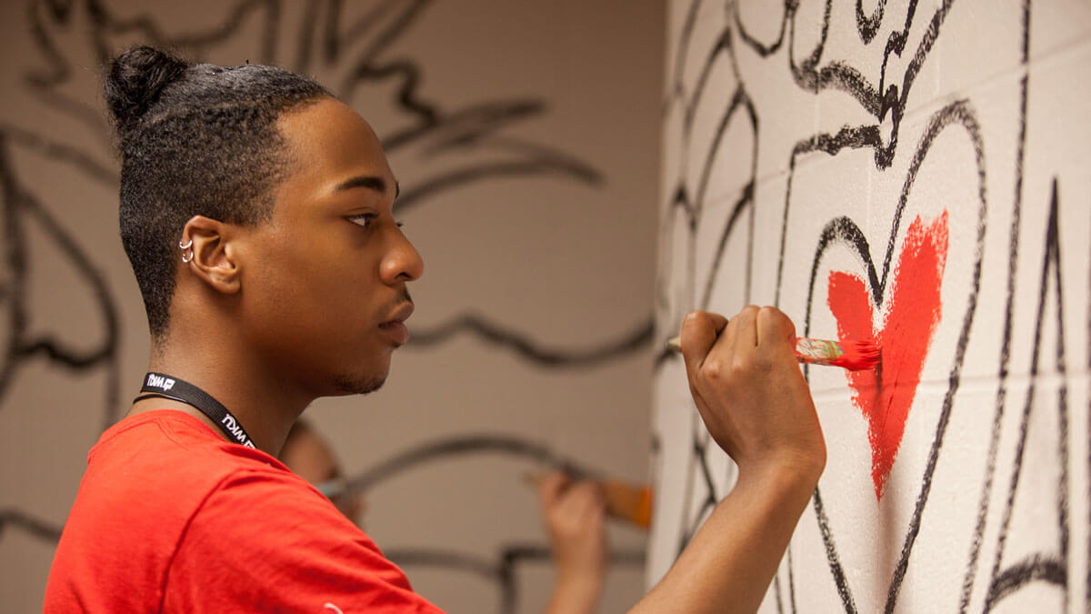 WKU student painting The Great Wall of Service mural project