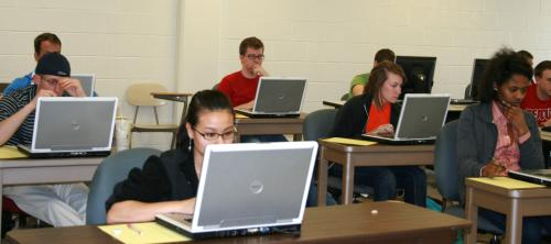 Accounting students studying with laptops.