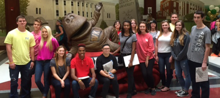 A tour group poses with the Big Red statue in DSU.