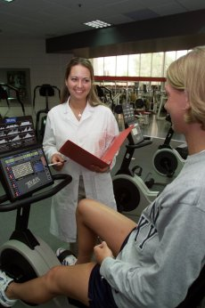 dietitian counseling student on exercise equipment