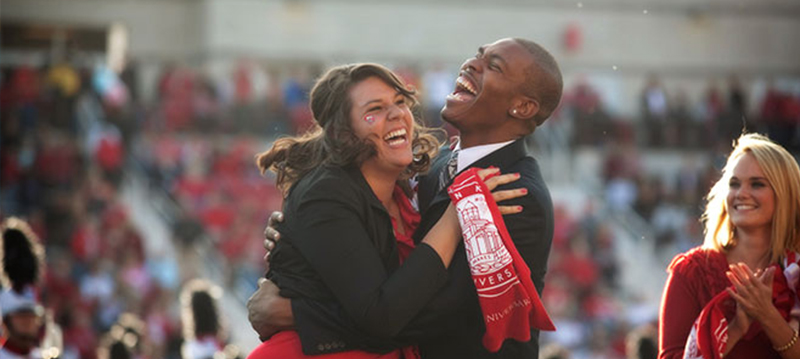 Image of two students hugging during homecoming on the WKU football field.