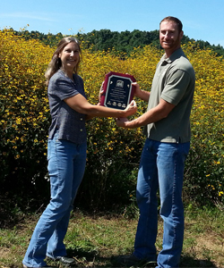 Nancy Givens presents John Seymour a plaque of recognition of Roundstones' services and supplies