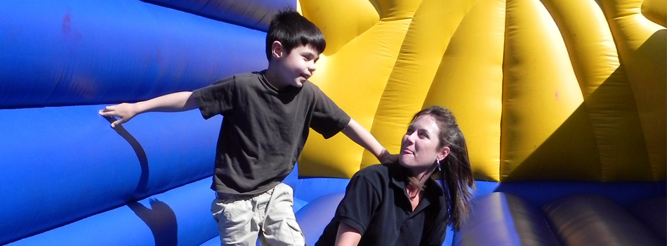Playing in the Bouncy House - A communication disorders graduate student interacts with children as they play in the bouncy house at the Clinical Education Complex Summit