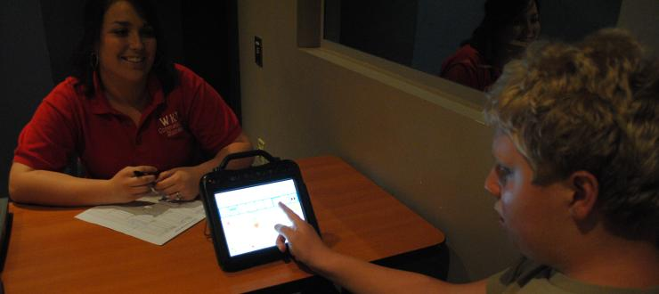 A Communication Disorders student during a therapy session with her client, using an Assistive Augmentative Communication device