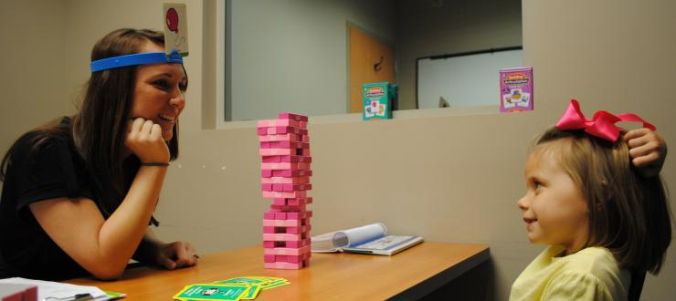 A communication disorders student plays jenga with her client during a therapy session.
