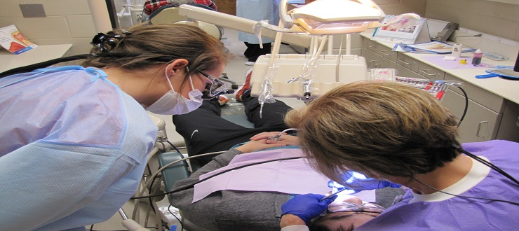 Dental Hygiene student works with faculty in clinic