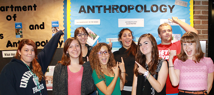Anthropology Club students having fun in front of the anthropology bulletin board
