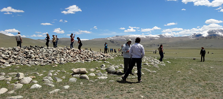 Anthropology students and faculty investigating a Bronze Age stone mound in Mongolia