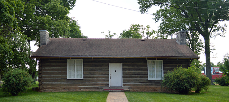 Image of the Pioneer log cabin from the front of the building