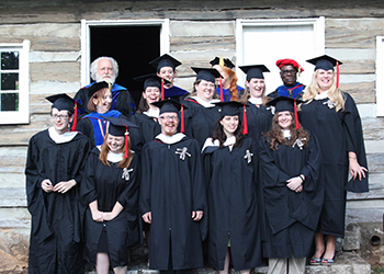 Graduates of the program standing in front of a log cabin