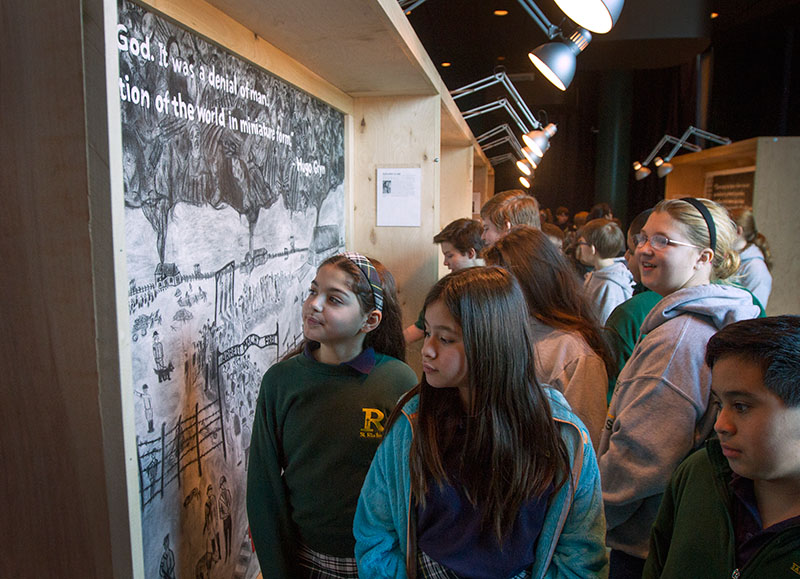 Students examine the VAMPY Holocaust murals during an exhibition at The Kentucky Center for the Performing Arts in Louisville. The murals were displayed in conjunction with performances of the play
