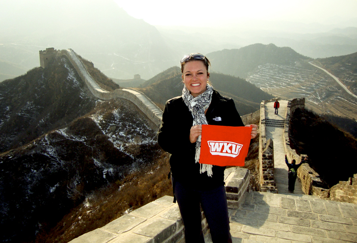 An Honors student displays her red towel on the Great Wall of China.