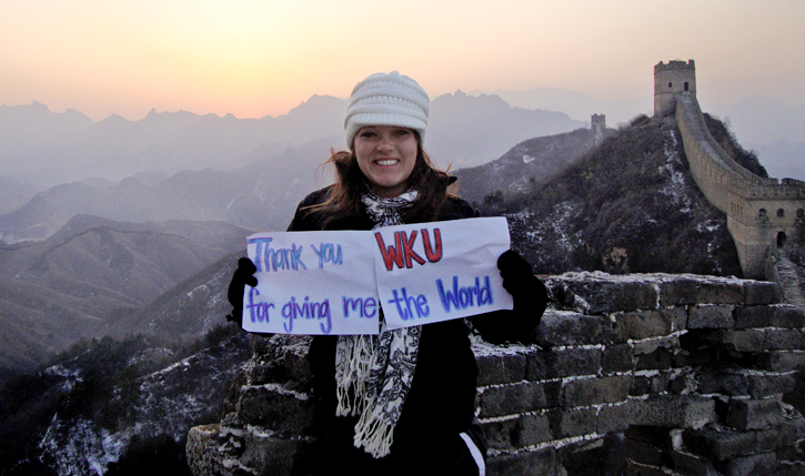 AN Honors student holds a sign saying 'Thank you WKU for giving me the world' while standing on top of the Great Wall of China.
