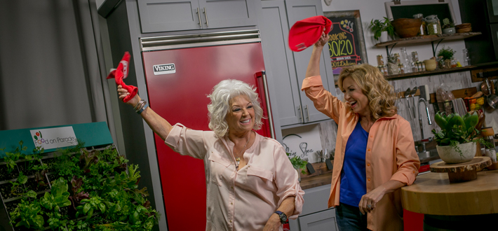 Robin Shea, host of Cooking 80/20, and her special guest Paula Deen proudly wave the Red Towel during a taping of the show that is filmed at the WKYU studios on the campus of WKU.