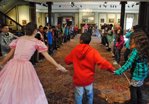 costumed docent and students dancing the virginia reel