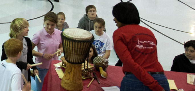 Children trying traditional African American instruments with teacher