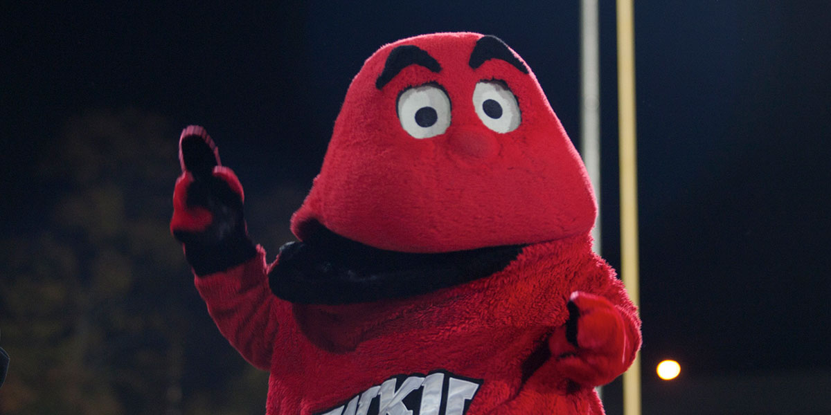 "Big Red holding up a ""number one"" finger at night on the football field"
