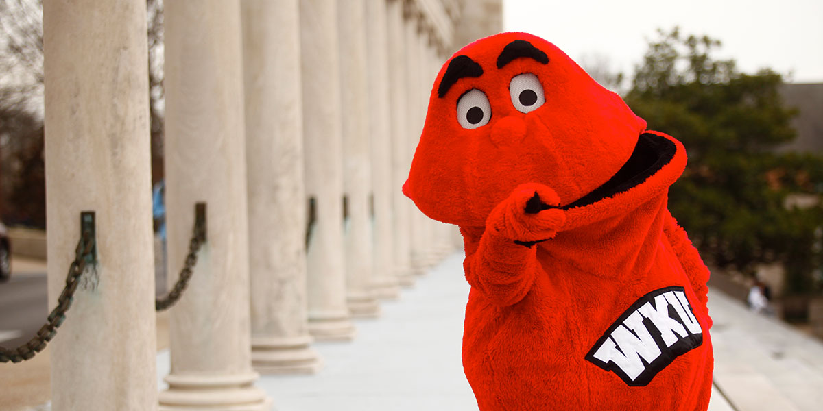 Big Red pointing very dramatically at the Colonnade on WKU's main campus