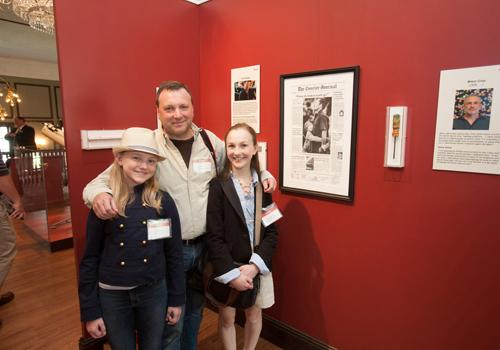 Tim Broekema, with his daughters Kacey and Gabi, stand before his display in the exhibit. He was a picture editor in Louisville when the newspaper editorial staff won a Pulitzer Prize for team coverage of the Carrollton, Ky bus crash.