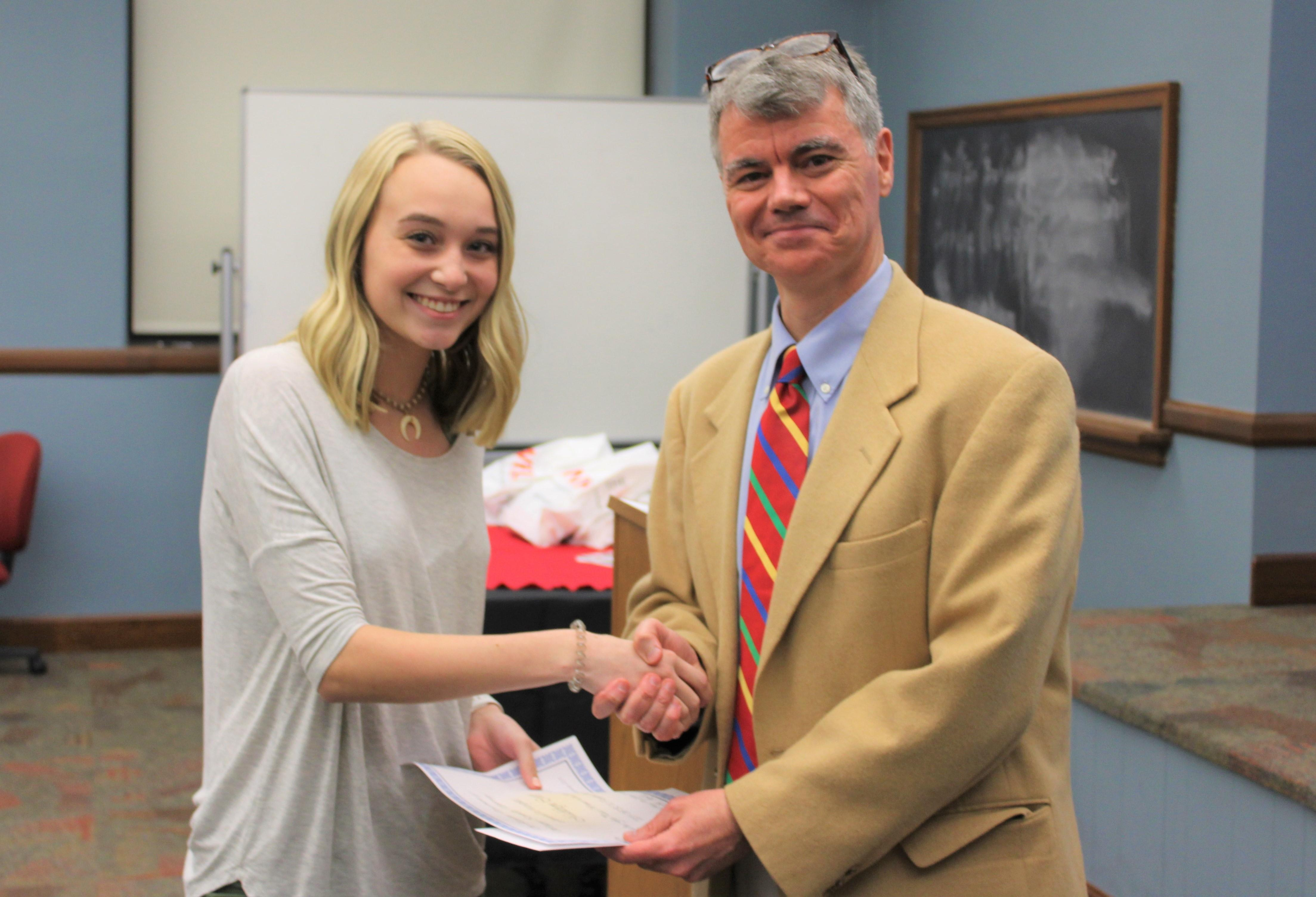 Dr. Hale shaking hands with 1st place Composition winner, Madelyn Curry