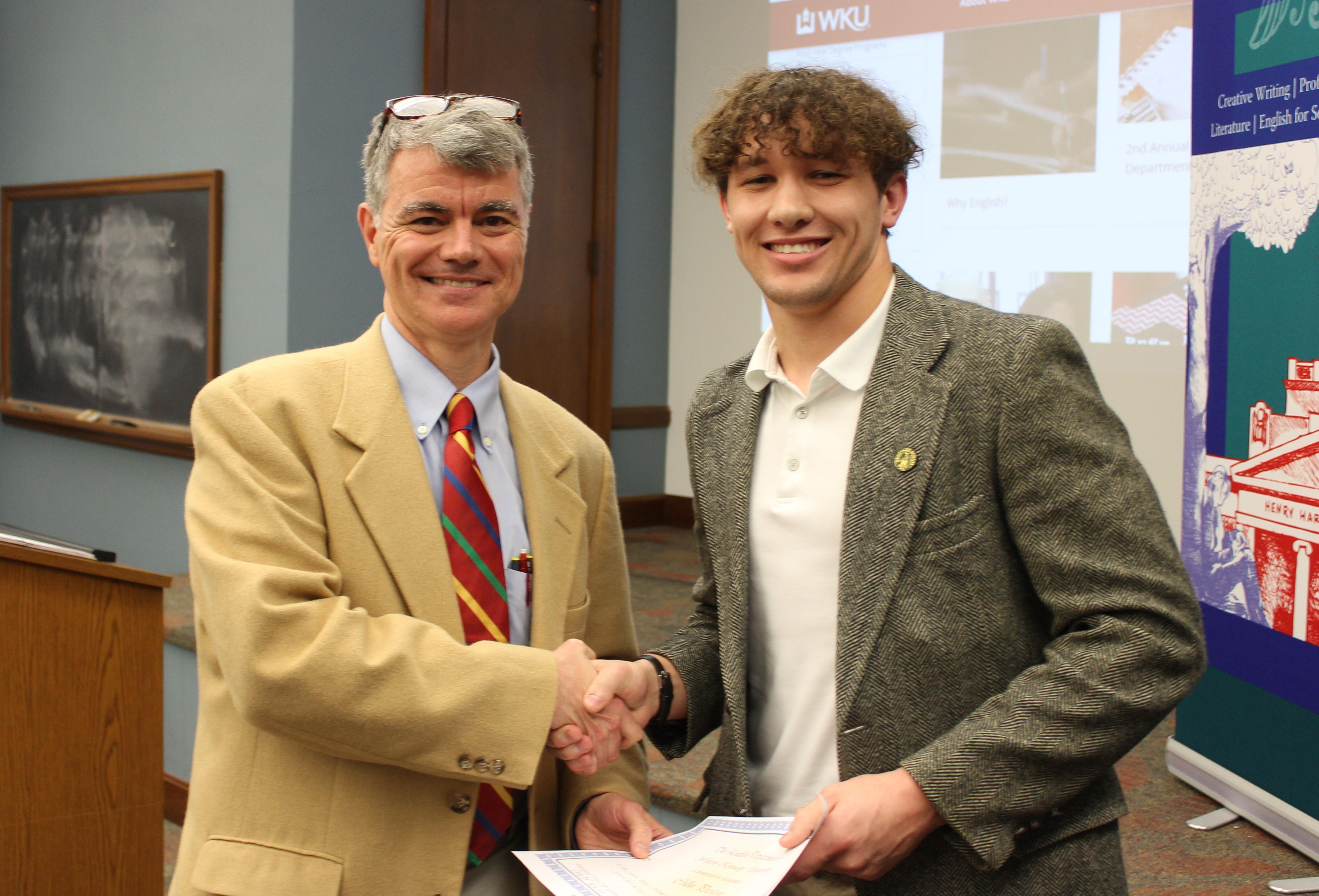 Dr. Hale shaking hands with 1st place Creative Writing winner, Collin Preston