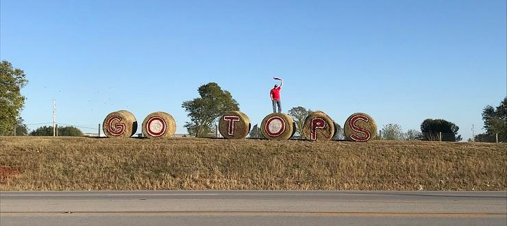 Dr. Woosley on hay bales for Homecoming