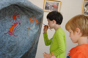 Campers painting symbols on rock ledge