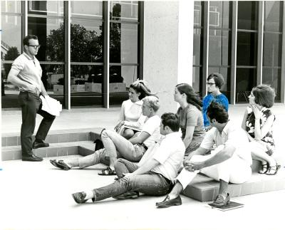 Students listening to a psychology lecture outside.