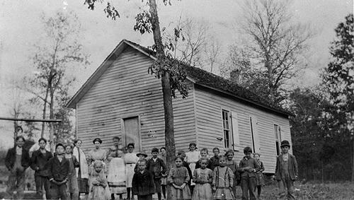 "Lost Creek School, on its one-acre lot, sat among ""plenty"" of trees. Schoolteachers between 1909 and 1922 included: Cora Sherry (1909-10); Norma Gibson (1911); Rochester Watt (1912); Mrs. Claudia _____ (1913); Herbert Jones (1914-15); Mattie Biggerstaff (1916); Elacia Willis (1919); Lorene Nicols (1920); Fred Burnett (1921); and, W.G. Vaught (1922). (Courtesy of Library Special Collections, WKU)"