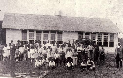Warren County's first Rosenwald School opened July 16, 1923 in the Cox Springs District. The two-teacher facility, located outside the western edge of Bowling Green, had two classrooms measuring 22' x 30', each with its own entrance and vestibule, two cloakrooms and a 12' x 12' community room. Reverand Henry D. Carpenter stands with students posed in front of the schoolhouse. (Courtesy of Library Special Collections, WKU)