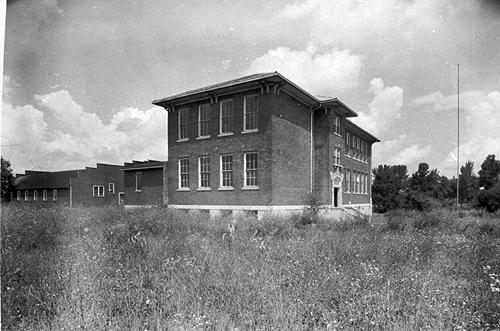 In 1926, the county built a new Oakland School. The two-story structure had five classrooms, a library, principal's office, lunch room and a basement. Oakland's gymnasium, shown at the rear of the main structure, was built in 1927. By 1932-33, Oakland offered four years of high school work. (Courtesy of Library Special Collections, WKU)