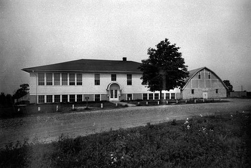 In 1927, an eight-room schoolhouse was built. It was lit primariliy with electricity but had a gas jet in the hall on the first floor. Constructed the same year, the designs of the Hadley and Richardsville schools were almost identical. By 1932-33 Richardsville offered a four-year course of study in high school work. Built in 1936, the gymnasium shown to the right had a box platform stage on the first floor. It's basement contained a brick forge, anvil, woodworking bench, electric saw, and emery wheel. (Courtesy of Library Special Collections, WKU)