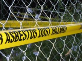 Asbestos warning tape on fence