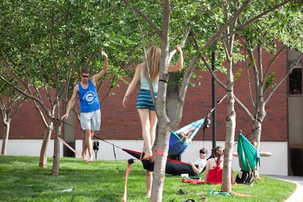 Students enjoy slacklining and hammocks outside Minton Hall
