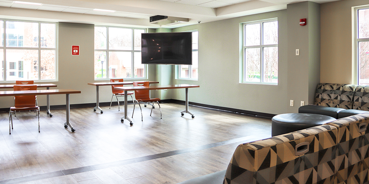 tables, chairs, couches, and television in Southwest Hall common room