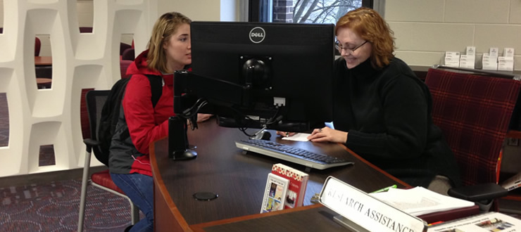 Librarian Lisa Miller helps student at the Research Assistance Desk in the Commons.