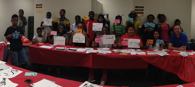 Area high school students participate in a SWAG (Start with a Goal) event led by Arabic instructor, Lhousseine Guerwane (front row, right).