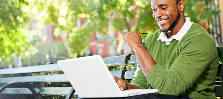 Online learner studying outside on a park bench with a laptop