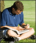 man studying in park with laptop