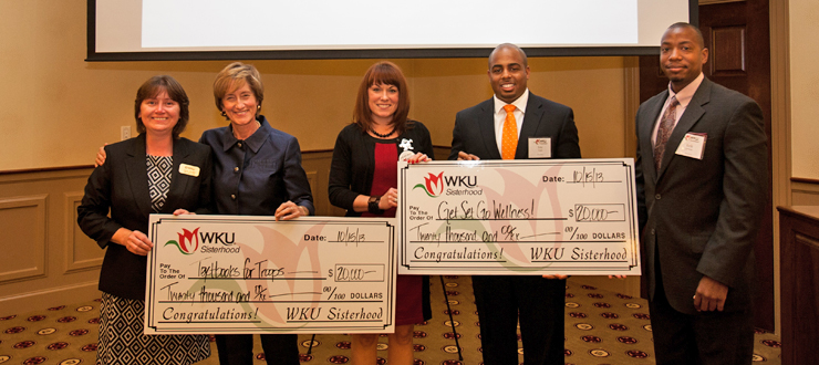 "The WKU Sisterhood organization made their annual grant award Oct. 15 to two different WKU projects. Co-chairs Mrs. Julie Ransdell and Ms. Kristen Miller presented $20,000 checks to the ""Textbooks for Troops"" program, represented by Tonya Archey, and the ""Get Set Go Wellness Program,"" represented by Erik Jenkins and Eric Logan."