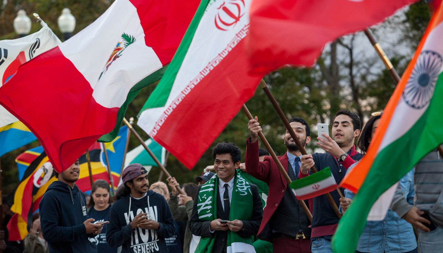 international students carrying flags at homecoming