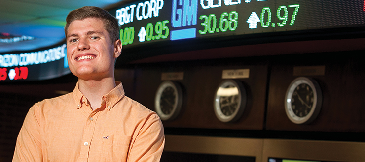 Finance student in front of ticker