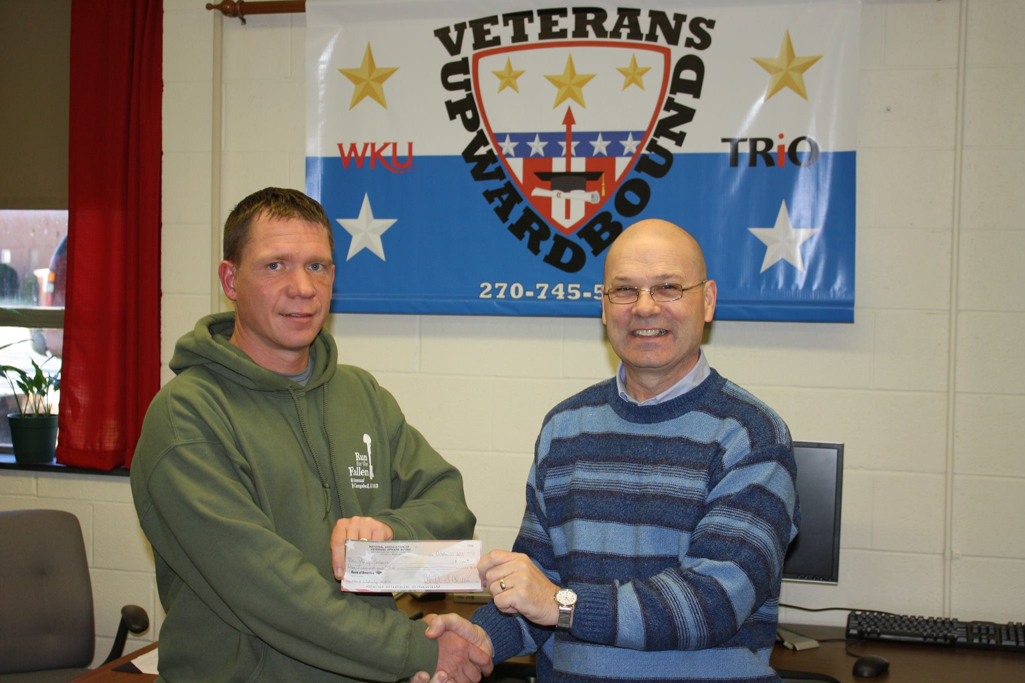 VUB alumnus Phillip Parsons receives his check from Counselor Rick Wright